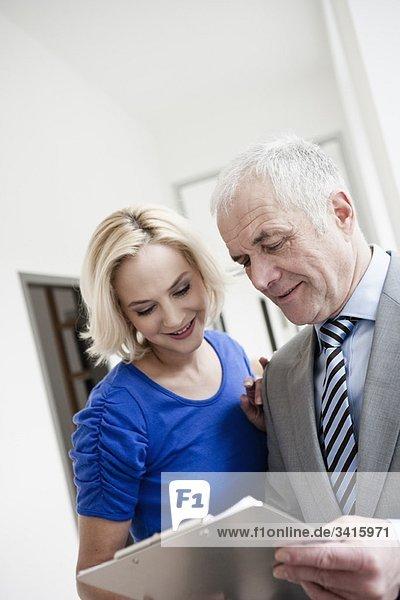 Geschäftsmann und Frau mit Klemmbrett