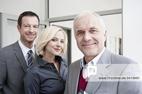 3 Geschäftsleute mit Blick auf die Kamera