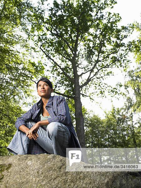 Frau sitzt auf einem Felsen  im Wald