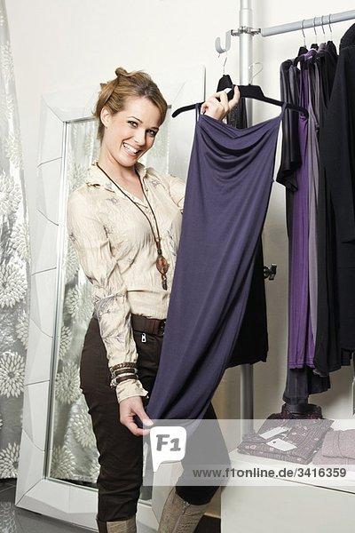 Eine Frau hält ein neues Kleid hoch.