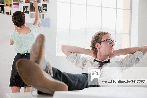 Modedesignerin auf Stuhl sitzend  Hände hinter dem Kopf Modedesignerin auf Stuhl sitzend, Hände hinter dem Kopf