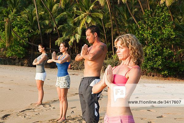 Menschen Übendes Yoga am Strand