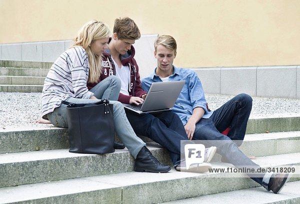 Drei Schüler sitzen auf einer Steintreppe mit Laptop