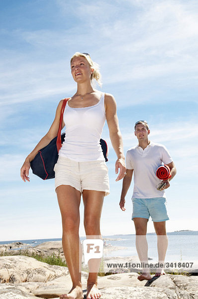 Two young people walking on the beach