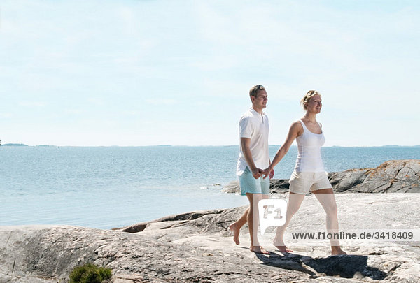Young cople walking on the rocks beside the water