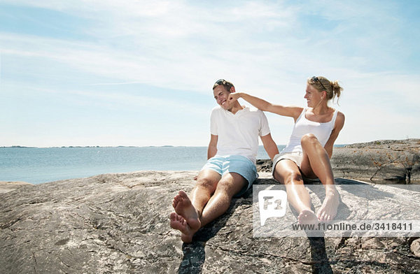 Young couple sitting on the rock by the water