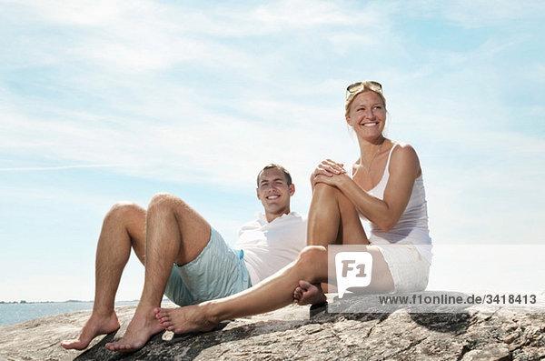 Junges Paar am Strand sitzend