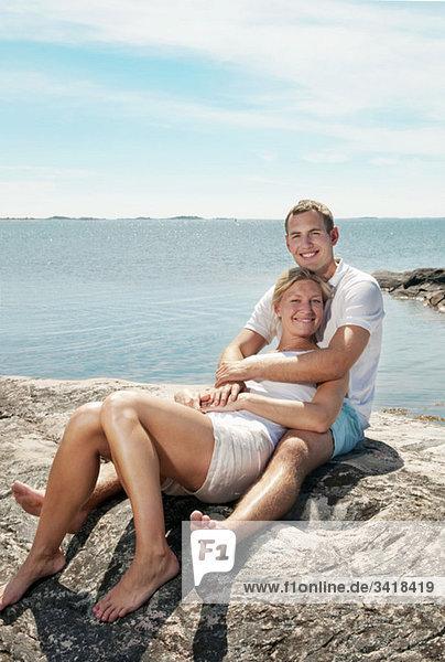 Süßes Paar am Strand sitzend