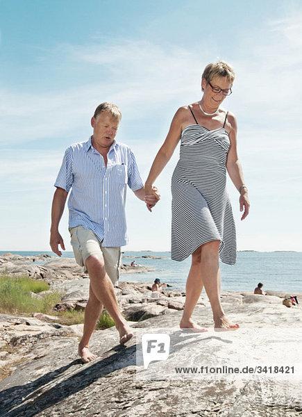 Ältere Paare beim Spaziergang am Strand