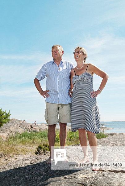 Zwei glückliche Menschen  die am Strand stehen.