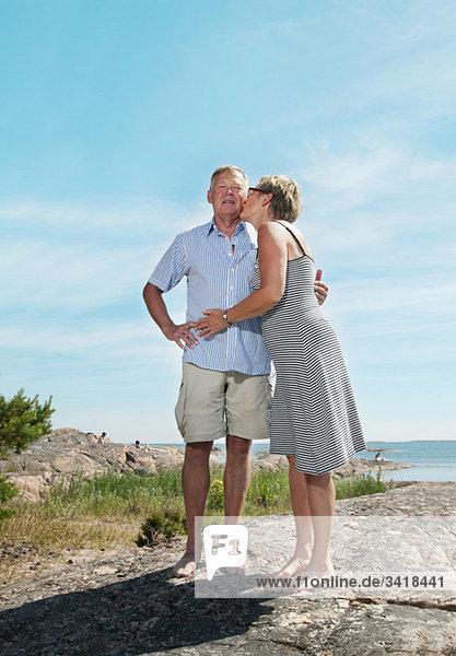 Zwei zärtliche Menschen  die am Strand stehen.