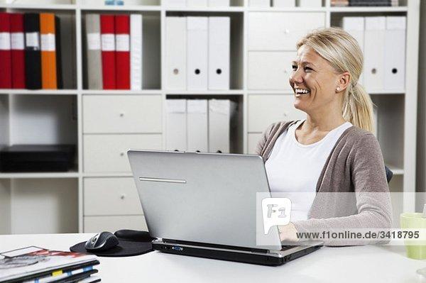Glückliche Geschäftsfrau sitzend am Laptop