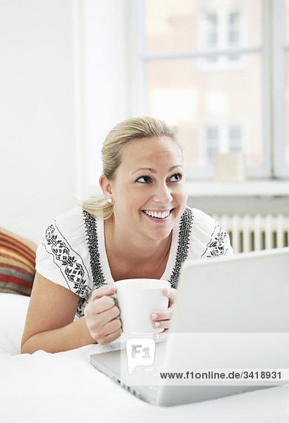 Glückliche Frau mit Computer und Kaffee Glückliche Frau mit Computer und Kaffee