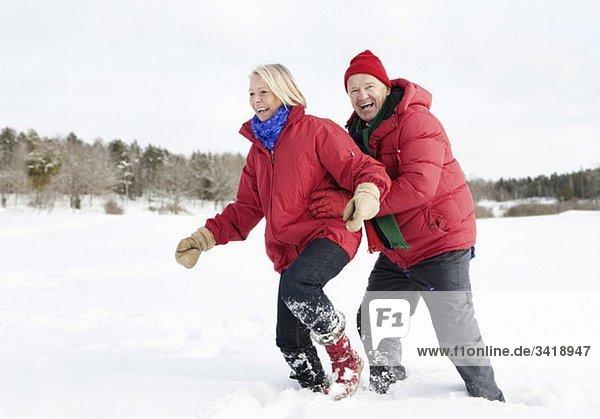 Zwei ältere Menschen  die durch den Schnee rennen.