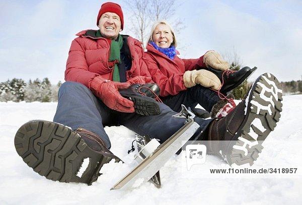 Zwei Menschen sitzen im Schnee Zwei Menschen sitzen im Schnee