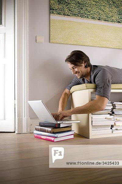 Mann liegt auf einem Regal und benutzt ein Notebook  Flachwinkelansicht