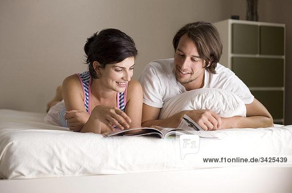 Mann und Frau lesen eine Zeitschrift im Bett  Flachwinkelansicht