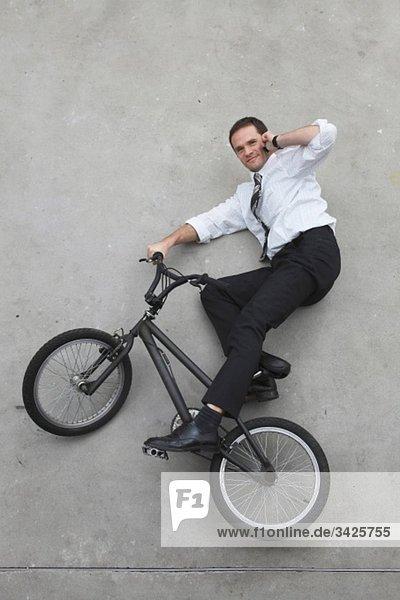 Geschäftsmann auf dem Fahrrad mit dem Handy  erhöhte Aussicht Geschäftsmann auf dem Fahrrad mit dem Handy, erhöhte Aussicht