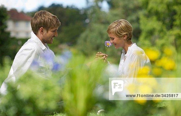 Junges Paar im Freien  Frau mit Blume  lächelnd  Porträt