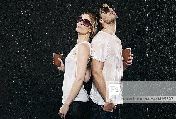 Männer und Frauen stehen Rücken an Rücken  im Regen  halten Einwegbecher.