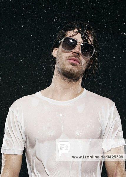 Ein Mann  der im Regen steht und eine Sonnenbrille trägt.