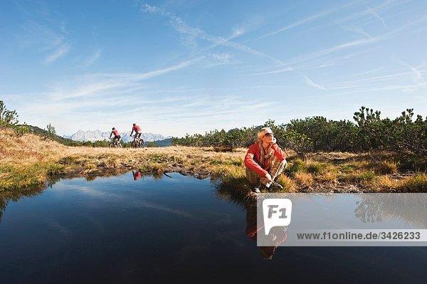 Österreich  Salzburger Land  Frau entspannt am See  Biker im Hintergrund