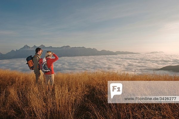 Austria  Steiermark  Reiteralm  Hikers admiring view over clouds