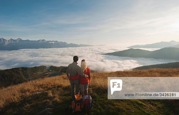 Austria  Steiermark  Reiteralm  Couple of hikers admiring view over clouds  rear view