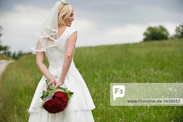 Die Braut hält einen Blumenstrauß hinter ihrem Rücken und lächelt.