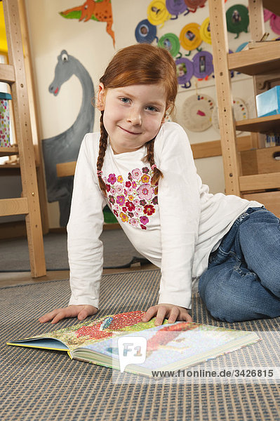 Germany  Girl (6-7) in nursery with book looking into camera  smiling  portrait