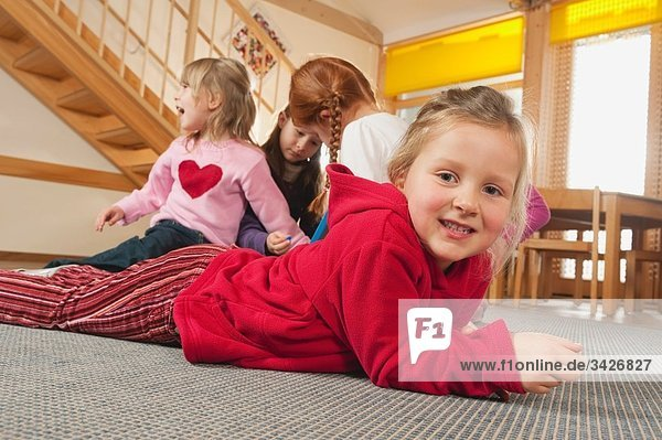 Germany  Children in nursery  girl (6-7) lying on floor  children in background playing together