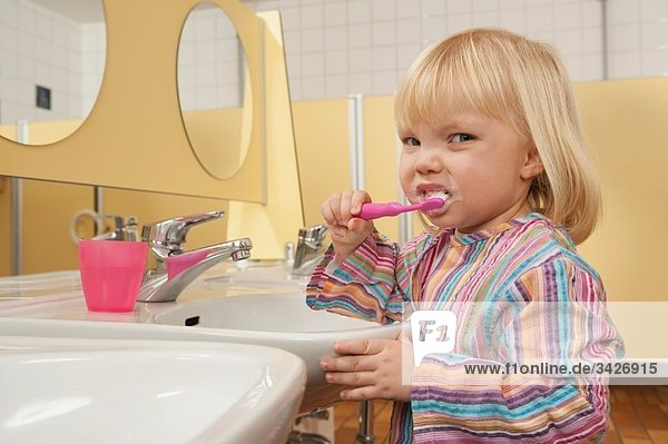 Germany  Girl (3-4) in lavatory brushing her teeth  side view  portrait  close-up