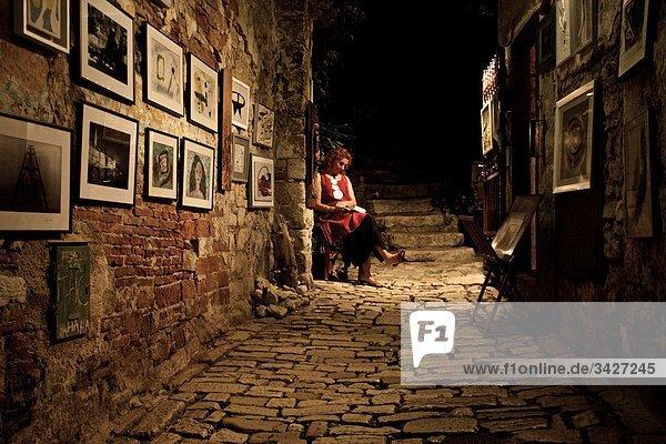 Frau in einer Gasse sitzend  Bilder hängen an der Wand  Kroatien