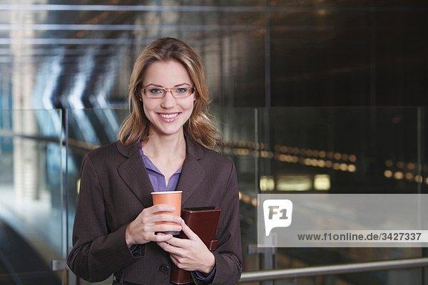Geschäftsfrau in der U-Bahn-Station mit Pappbecher  lächelnd  Portrait