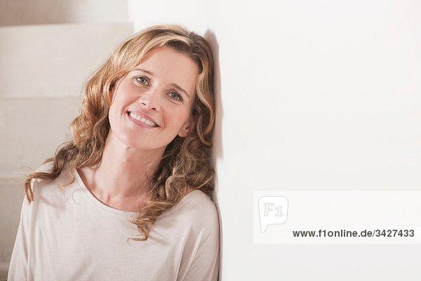 Frau an die Wand gelehnt  lächelnd  Portrait  Nahaufnahme