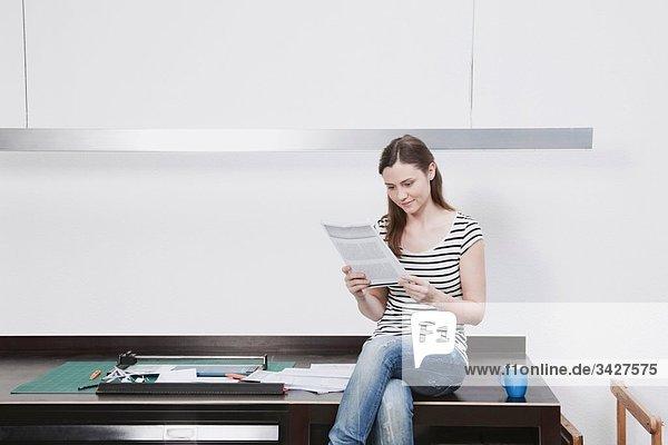 Woman sitting on desk reading document.