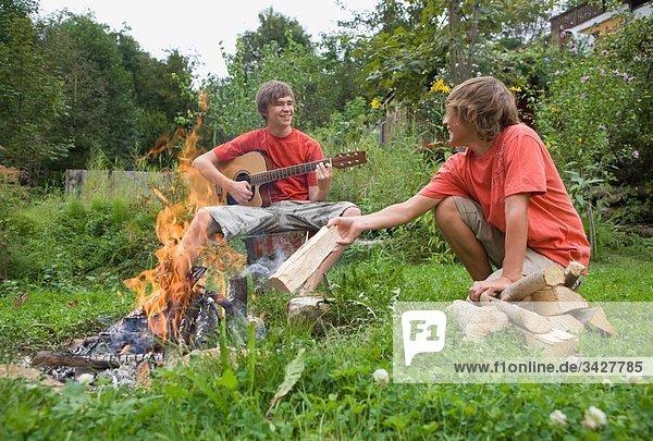 Austria  Salzburger Land  Teenage boys (14-15) in garden  sitting at campfire