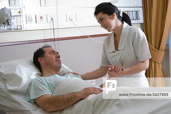 Krankenschwester  die sich um den Patienten kümmert