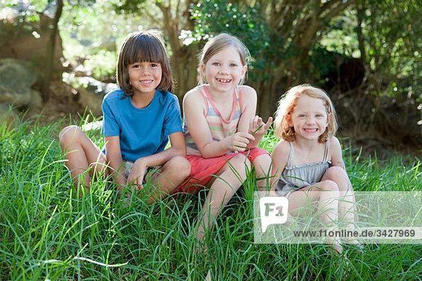Drei Kinder sitzen auf Gras