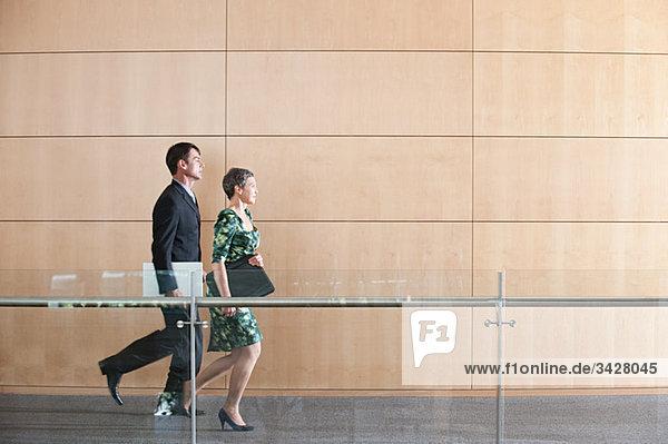 Geschäftsleute  die durch den Korridor laufen