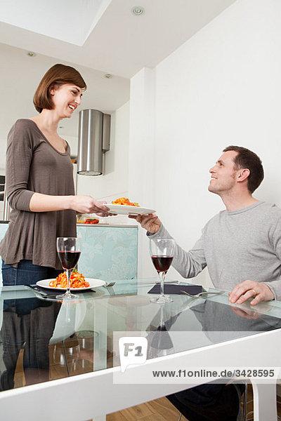 Frau übergibt Teller an Ehemann