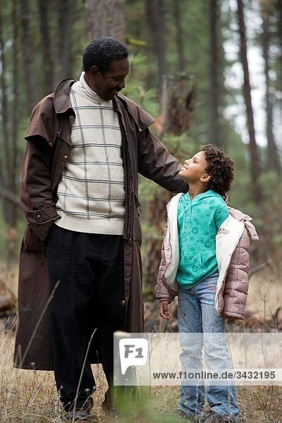 African American Father and Daughter  young child  enjoy each other's company walking through a forest with the little girl stopping to look up at her father.