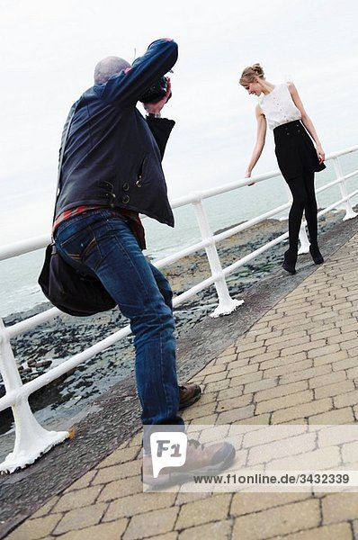 A male fashion photographer taking photographs of a slim female model  outdoor location  UK