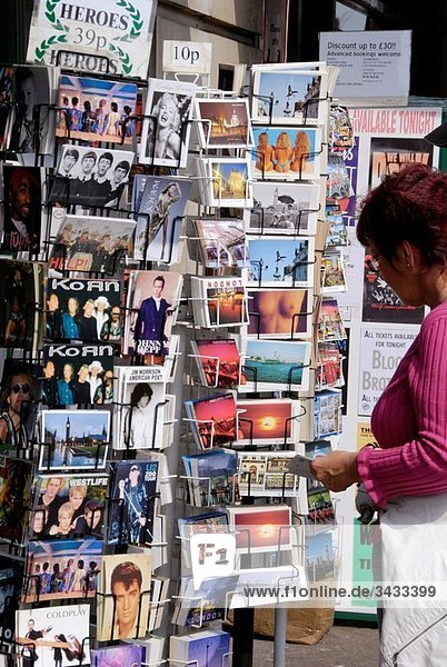 Woman looking at London tourist postcards on a stand