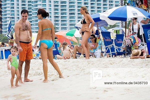 Local people and tourist along Barra da Tijuca Beach in Rio de Janeiro in Brazil