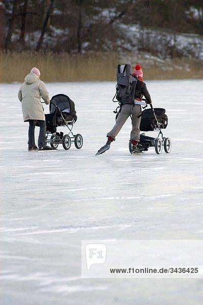 Rückansicht des zwei Frauen Eislaufen mit ihrem Baby-Buggys