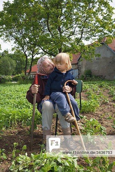 Großmutter mit ihrem Enkel zusammensitzen auf Stuhl im Kartoffelfeld