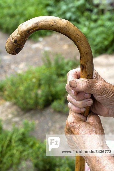 Hände der eine alte Bäuerin halten einen Gehstock. Tschechische Republik