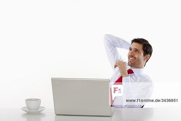 Junge Geschäftsmann in weißen Hemd hinter Schreibtisch mit laptop