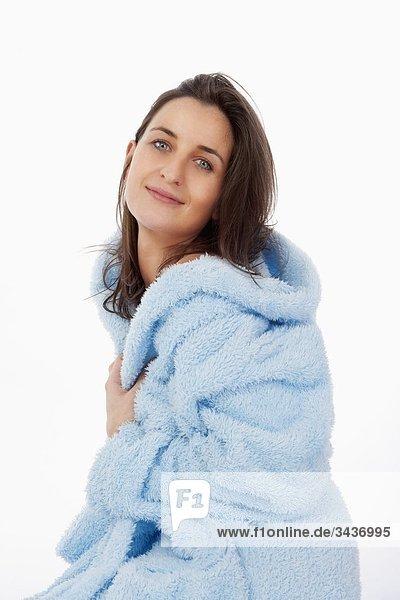 Eine Frau in blau Bademantel mit Kapuze. Isoliert auf weiss